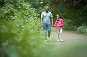 Father and daughter holding hands on path in woods