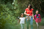 Mother and daughters hiking on trail in woods