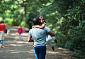Playful father carrying happy daughter on trail