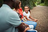 Happy family talking on park bench