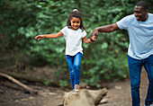 Father helping daughter balance on fallen log
