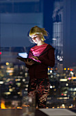 Young businesswoman with tablet at office window