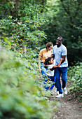 Happy family hiking on trail in woods