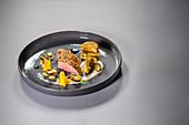 Challans duck with bean cream, porcini mushrooms, peach and brioche dumplings