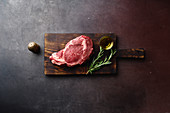 Raw black angus prime rib eye beef steak on wooden cutting board