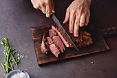 Male hands cutting cooked until medium ribeye steak on wooden cutting board
