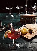 Red alcohol cocktail with splashes served in coupe glass garnished with lemon on bar counter