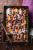 Pfirsich-Heidelbeer-Kuchen vom Blech mit Puderzucker