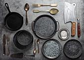 Altes Vintage-Geschirr, Besteck und Küchenutensilien auf Steinuntergrund