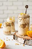 Orange yoghurt with granola in jars