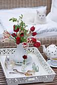 Tulpenstrauß mit Wildrosenzweig auf weißem Holztablett