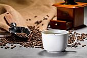 Kaffeetasse, Kaffeebohnen, alte Kaffeemühle und Jutesack