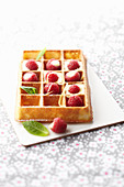 A waffle with lemon cream and raspberries