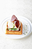 A waffle with bresaola, apple and beans