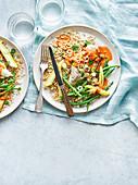 Hähnchenbrust mit pikanter Erdnusssauce auf Reis und Gemüse