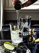 Cocktail mit Wodka, Limette, Brombeeren und Minze zubereiten