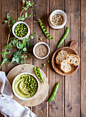 Hummus made with green pea on wooden table with ingredients and bread slices