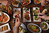 Verschiedene pikante thailändische Speisen auf Holztisch, Hände mit Essstäbchen