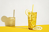Glass of fresh beverage with lemons placed on table