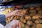 Frau im Supermarkt gibt Kartoffeln in recycelbaren Beutel
