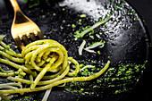 Spaghetti mit Pesto und Parmesan auf Gabel
