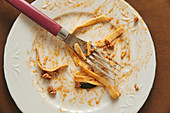 Empty white plate and fork smeared with food after eating delicious Bolognese pasta