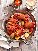Grilled small pork sausages in black beer marinade with potatoes