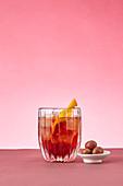 Drink mit Eiswürfeln und Zitrone vor rosa Hintergrund