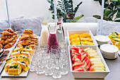 Assorted smoothie in glass bottles and sandwiches with slices of bacon and sweet croissants, empty glasses for party