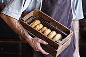 Male baker with wooden box full of freshly baked doughnuts