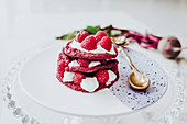 Organic beet pancakes with fresh raspberry on plate with golden spoon on white table