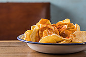 Pile of crispy potato chips in bowl placed on wooden table at home