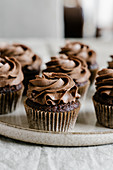 Appetizing sweet chocolate cupcakes with chocolate butter cream served on round tray on table