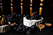 A black counter with brie with concord grapes, figs, blackberries and thyme