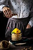 Ein Stapel Pancakes mit Birnen und Ahornsirup