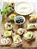 Canapés with chickpea cream, radishes and olives