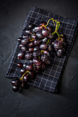Bunch of delicious sweet ripe red grapes placed on checkered napkin on black surface