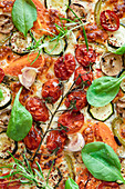 Palatable vegetarian pizza with cherry tomatoes and mushrooms garnished with fresh basil and rosemary