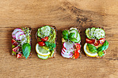 Toasts with radish and lemon slices garnished with basil sprigs and placed on wooden table in kitchen