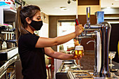 Side view of female barman in black mask pouring foamy beer on beer column