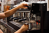 Side view of unrecognizable female barista using coffee machine and preparing aromatic coffee in cafe