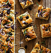 Focaccia with black olives and herbs on wooden table