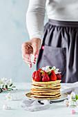 Ein Stapel Pancakes dekoriert mit frischen Erdbeeren