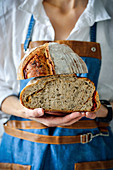 Woman is holding a large loaf of sourdough bread in her hands