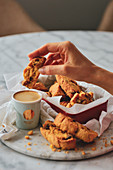 Hand with a cookie and a cup of coffee