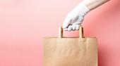 Hand mit weißem Handschuh hält braune Papier-Einkaufstüte (Lieferservice)