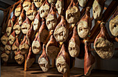Cured ham hanging in an ageing chamber