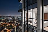 Wohnzimmer im modernen Hochhaus in abendlich beleuchteter Stadt