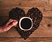 Anonymous person with mug of hot beverage placed on coffee beans in shape of heart