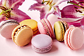 Assorted delectable macarons placed on pink table with fresh lily flowers